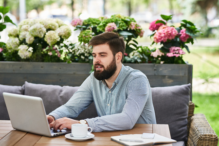 Portrait of contemporary bearded man using laptop working at table in comfortable cafe lounge outdoors