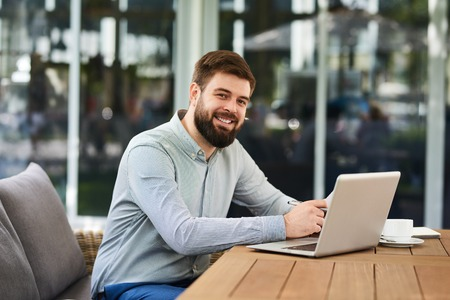Portrait of successful young businessman looking at camera and smiling while working with laptop in modern office