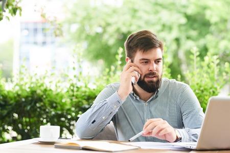 カフェ屋外で作業しながら電話で話す成功した青年実業家の肖像画