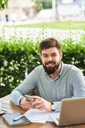 Portrait of young bearded businessman looking at camera and smiling while working in cafe outdoors Фото со стока