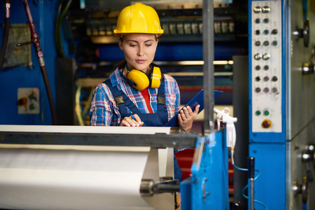 Portrait of beautiful woman checking machines  in modern factory working in quality control