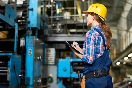 현대 공장 운영 기계를 확인하는 동안 클립 보드에 작성하는 여성 공장 노동자의 초상화