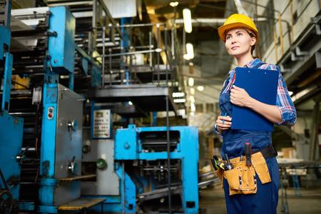 현대 공장에서 근무하는 젊은 여성의 초상화, 클립 보드를 들고 운영 기계 사이의 산책