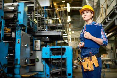 Portrait of young woman working in modern factory, walking between operating machines holding clipboard