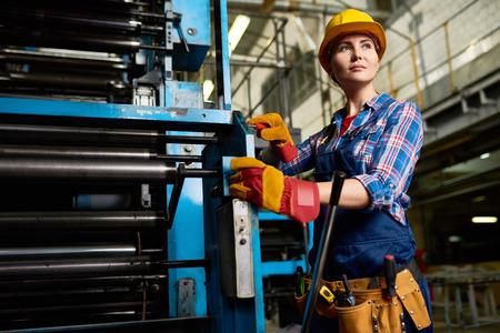 현대 공장에서 자신있게 멀리보고하는 기계 장치를 세우는 여성 공장 작업자의 초상 스톡 콘텐츠