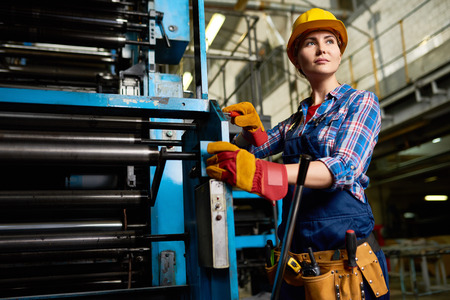 Portrait of female factory worker setting up machine units looking away confidently in modern plant