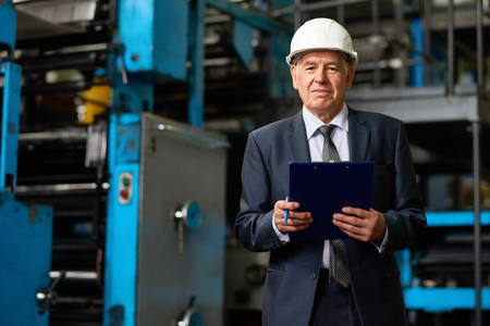 Portrait of senior factory owner  wearing hardhat on tour in modern factory looking at camera and smiling holding clipboard