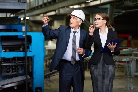 Portret van jonge vrouw die een reis van moderne fabriek geeft aan hogere investeerder of uitvoerende manager die bouwvakker draagt