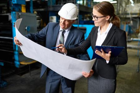 건설을 설명하는 젊은 비서 관리자와 현대 공장의 평면도를보고 수석 사업가의 초상화