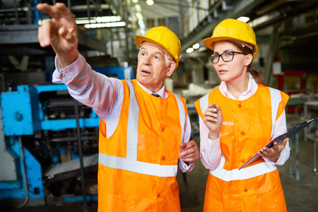 Portrait of senior factory worker explaining something to young woman pointing away at machines,  both wearing hardhats and reflective jackets