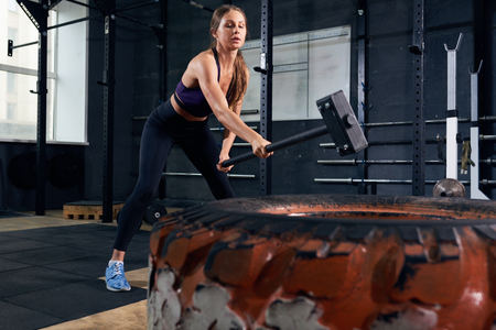 Portrait of strong young woman smashing large tire with sledgehammer during crossfit workout in modern gym