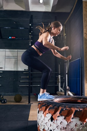 Side view portrait of strong young woman jumping on tire during crossfit workout in modern gym Stock Photo - 83831041