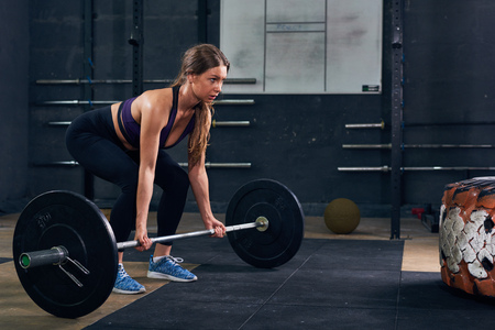 Portrait of strong young woman lifting heavy barbell during crossfit workout in modern gym