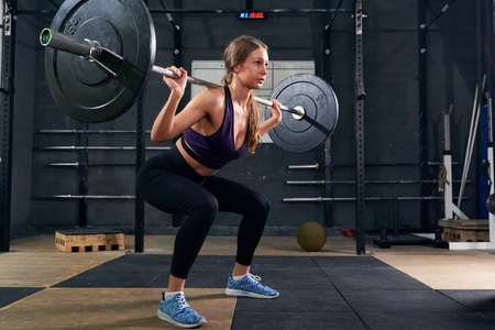 Portrait of strong young woman performing shoulder press with heavy barbell during crossfit workout in modern gym