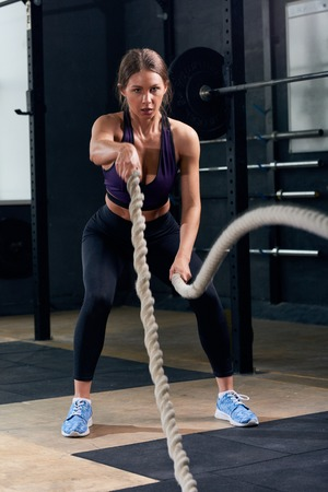 Portrait of strong young woman in heavy rope training during crossfit workout in modern gym Reklamní fotografie