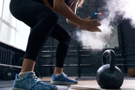 Side view closeup of unrecognizable young woman rubbing her hands with talk puffing cloud preparing to lift kettlebells during crossfit workout in modern gym