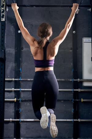 Achtermeningsportret van spier jonge vrouw die trekkracht UPS op bar uitvoeren tijdens crossfittraining in moderne gymnastiek