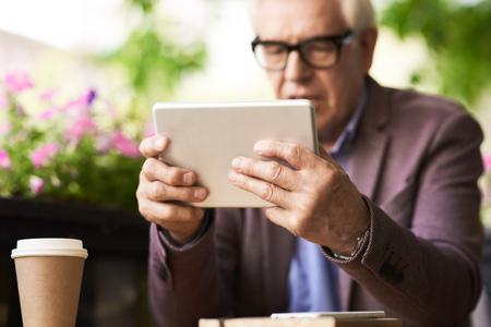 Portrait of senior man using digital tablet in outdoor cafe, focus on male hands holding modern device Stok Fotoğraf