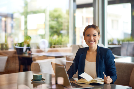Waist-up portrait of pretty Asian businesswoman with charming smile sitting at cozy small cafe and working on promising project, view through panoramic window