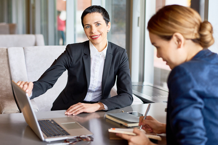 Waist-up portrait of pretty middle-aged entrepreneur looking at camera with charming smile while having project discussion with female coworker