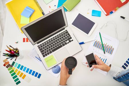 Above view of creative workplace of designer or freelance worker using laptop and smartphone on table with scattered supplies and color palette swatches Stock Photo