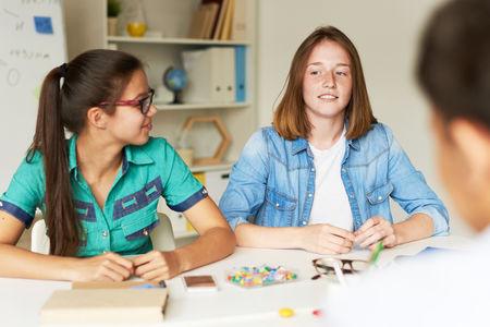 そばかすのティーンエイ ジャーがちと室内を集めながらの共同学校プロジェクトに関するアイデアを共有 写真素材
