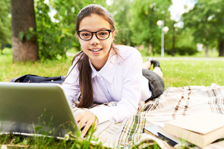 working on school project: Portrait of pretty dark-haired student looking at camera with wide smile while working on research paper with help of laptop, lovely public park on background