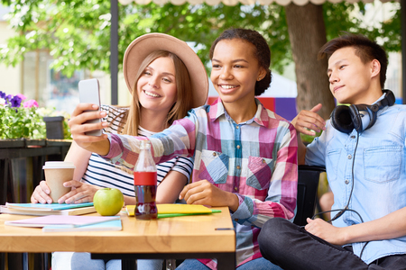 Multi-ethnic group of three  happy students taking selfie in outdoor cafe on sunny summer day