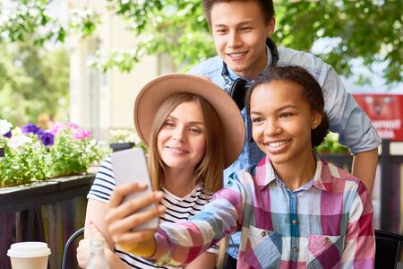 Multi-ethnic group of three  happy young people taking smartphone selfie in outdoor cafe on sunny summer day