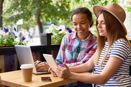 Portrait of two young women  using laptop and digital tablet in cafe smiling happily and looking at screen Stock Photo