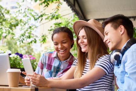 화창한 여름 날 야외 카페에서 노트북과 디지털 태블릿을 사용하는 젊은 사람들의 미소의 multi-ethnic 그룹