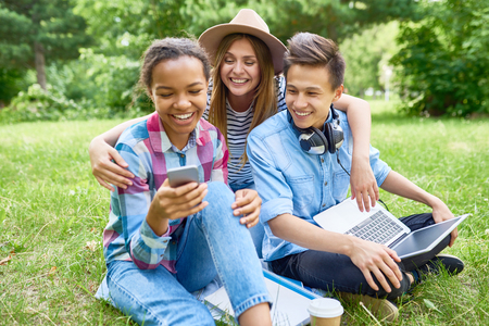Portrait of three  happy students sitting on green lawn and smiling looking at smartphone screen enjoying break on summer day Foto de archivo