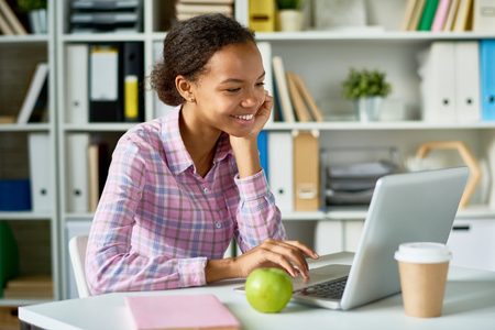 Portrait of smiling African girl studying using laptop in school library Banco de Imagens