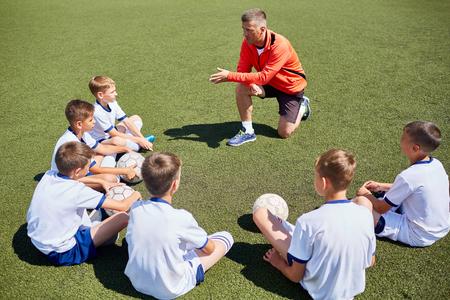 Junior voetbalteam zit rond coach luisteren naar lezing in het veld