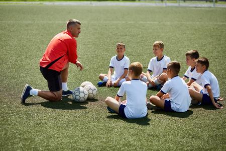 사전 게임 강연을 듣고 축구 필드에 코치 앞에 앉아 소년의 초상화 스톡 콘텐츠
