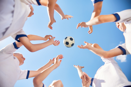 in low spirits: Low angle portrait of junior football team standing in circle with ball flying against blue sky Stock Photo