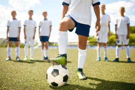 Porträt des niedrigen Abschnitts des unerkennbaren Fußballkapitäns, der in der Mitte des Feldes tritt auf Ball mit dem Rest des Teams im Hintergrund tritt Standard-Bild - 84229071