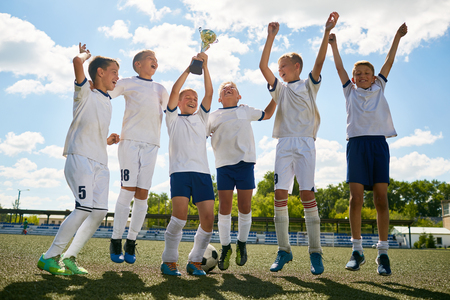 Portrait of junior football team cheering happily and jumping holding champions cup after winning match Stock Photo