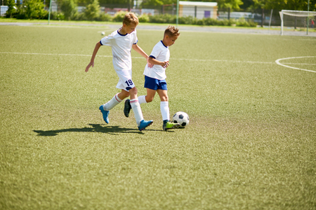 Portrait of two boys in uniform playing football during junior team practice in field
