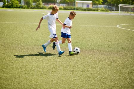 Portret van twee jongens in eenvormige speelvoetbal tijdens ondergeschikte teampraktijk op gebied
