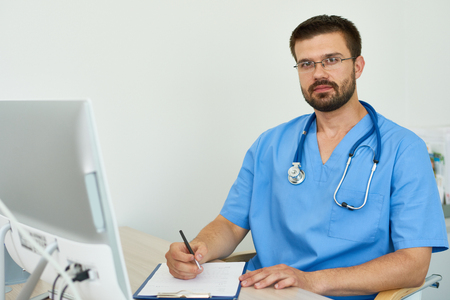 Portrait of experienced medical professional sitting at desk in doctors office filling in patient forms and looking at camera reassuringly against white background