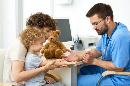 医師のオフィスで小さな子供を持つ若い母親の肖像画、女性持株チャイルズ腕の医師のオフィスで血液検査を取っています。