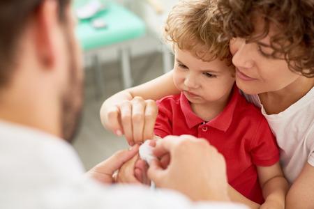 Portrait of adorable little boy with mother visiting doctor to bandage hurt finger 版權商用圖片