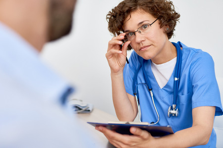 Portrait of young woman listening intently to patient filling in medical form at desk in doctors office