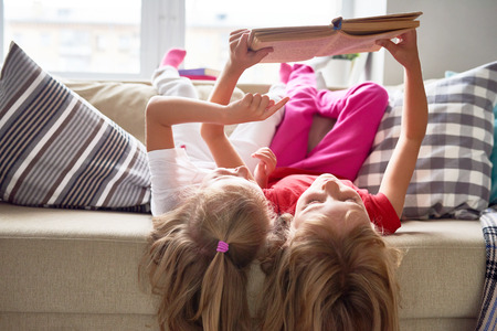Little Girls Reading Book at Home