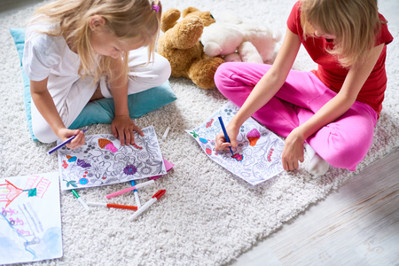 Meninas desenhando em livros para colorir no chão Foto de archivo - 84779446