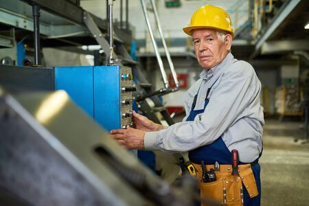 공장의 고위 근로자 운영 기계 장치