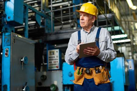 Hogere Fabrieksarbeider die Tablet gebruikt