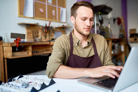 Jeweler using Laptop in Shop Stock Photo