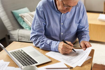 年配の男性が自宅のアプリケーション フォームに記入 写真素材